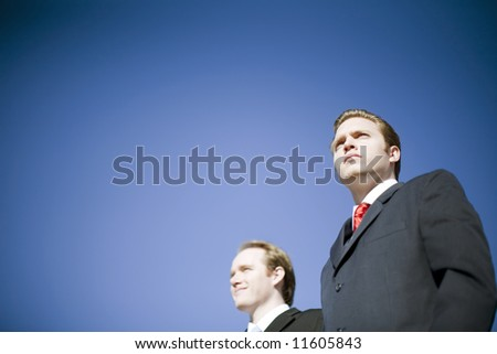 Two businessmen wearing suits posing with determined vision pose - stock photo