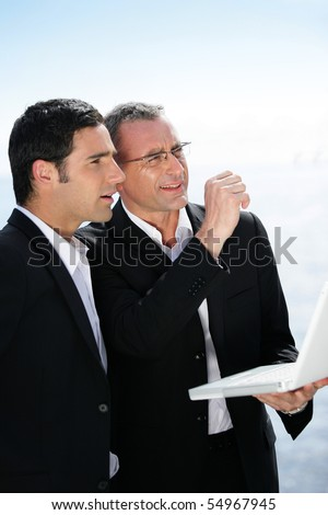 Two businessmen with a laptop computer looking away - stock photo