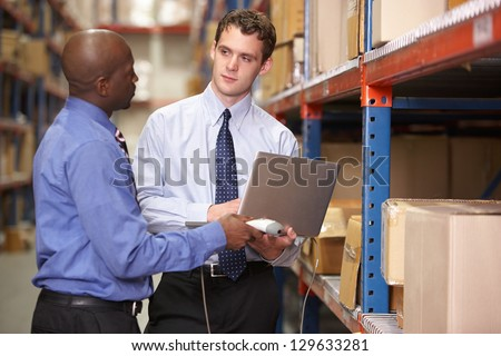 Two Businessmen With Laptop In Warehouse - stock photo