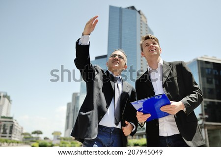 two businessmen working on a new project on background modern office corporate buildings - stock photo