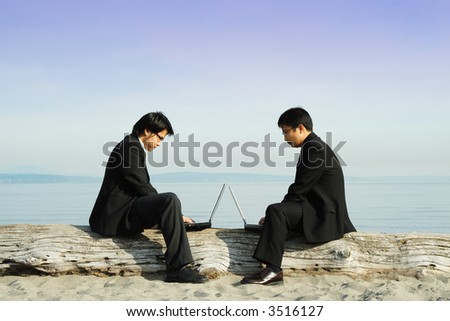 Two businessmen working on their laptops at the beach