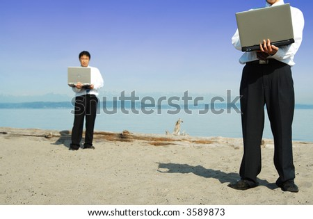 Two businessmen working together at the beach - stock photo