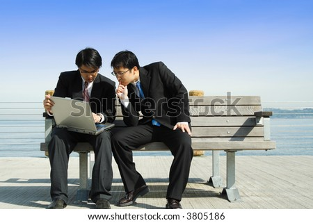 Two businessmen working together on a laptop - stock photo