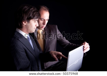 Two businessmen working together on a laptop, isolated on black background - stock photo