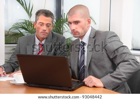 Two businessmen working together on a project - stock photo