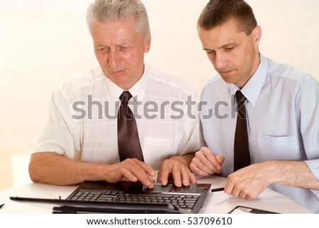 Two businessmen working together on a white