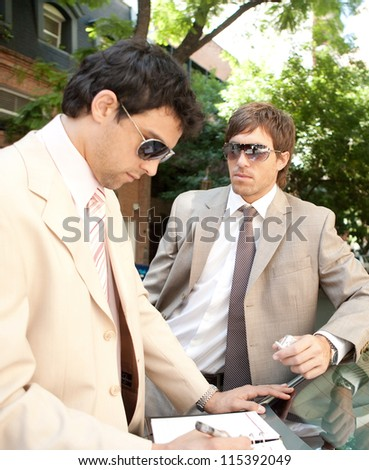 Two businessmen working while leaning on a car in a tree lined street in the city. - stock photo