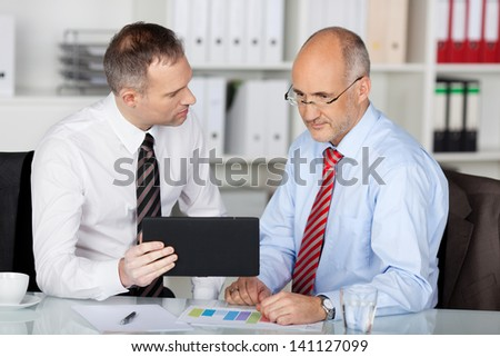 Two businessmen working with table at the office - stock photo