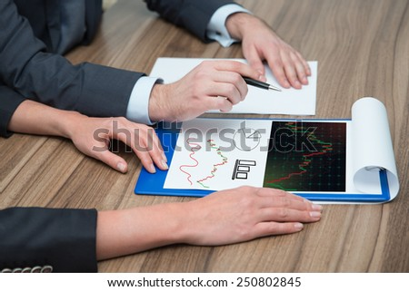 two businesspeople analyzes stock charts, close up - stock photo