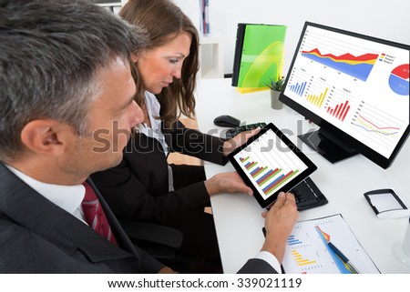 Two Businesspeople Analyzing Graph On Digital Tablet In Office - stock photo