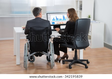 Two Businesspeople Analyzing Statistical Graph On Computer In Office - stock photo