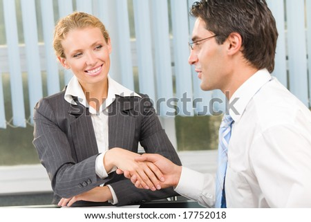 Two businesspeople cheering by handshake or flirting at office - stock photo