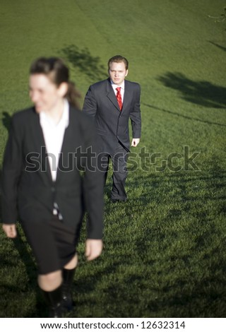 Two businesspeople climbing hill together wearing full suits and smiling - stock photo