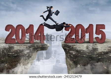 Two businesspeople cooperate through an obstacle from number 2014 to 2015 - stock photo