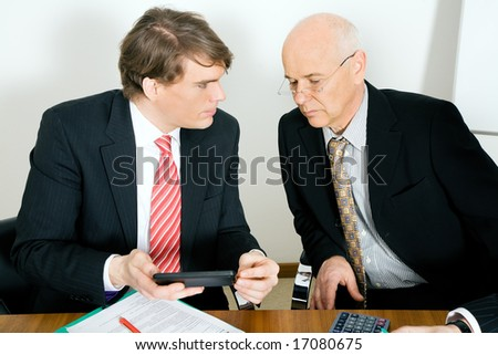 Two businesspeople crunching the numbers, the senior guy looking sceptical - stock photo