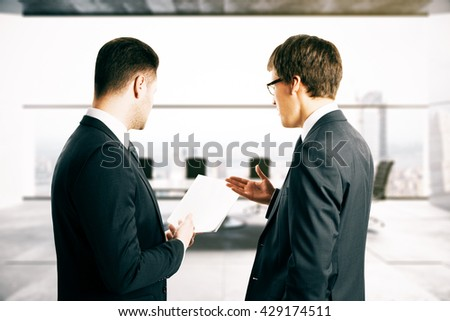 Two businesspeople discussing contract terms in blurry conference room interior - stock photo