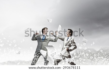 Two businesspeople in anger fighting with each other - stock photo