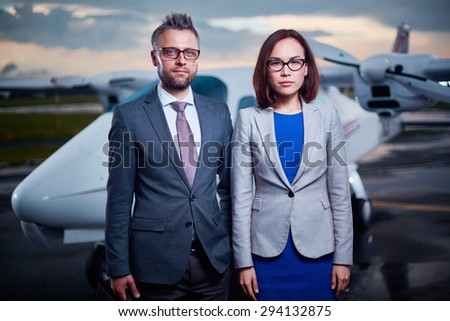 Two businesspeople in formalwear looking at camera outdoors  - stock photo