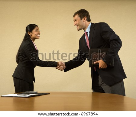 Two businesspeople in suits shaking hands and smiling.