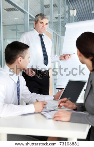 Two businesspeople listening to a teacher at the seminar