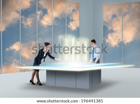 Two businesspeople looking at hologram of construction project - stock photo