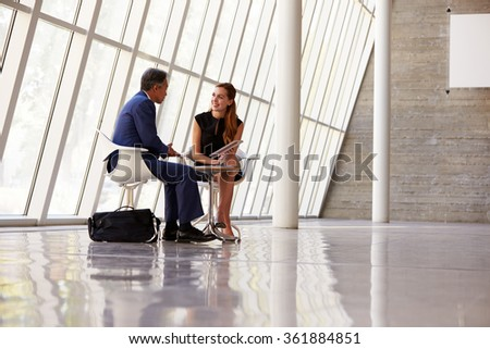 Two Businesspeople Meeting In Reception Of Modern Office - stock photo