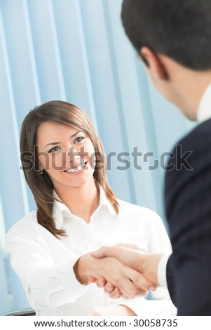 Two businesspeople, or business person and client handshaking at office