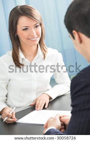 Two businesspeople, or business person and client, with document at office - stock photo