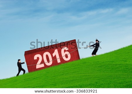 Two businesspeople removing a block as an obstacle with numbers 2016 on the hill under blue sky - stock photo