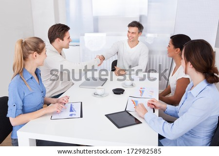 Two Businesspeople Shaking Hand In Front Of Coworker In A Conference Room - stock photo