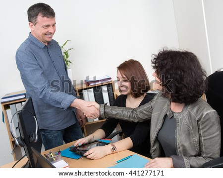Two Businesspeople shaking hand in front of female colleague In Office - stock photo