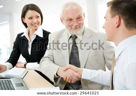Two businesspeople shaking hands in a modern office