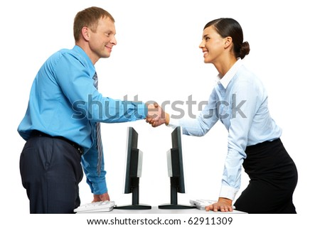 Two businesspeople shaking hands standing at two identical tables with computers
