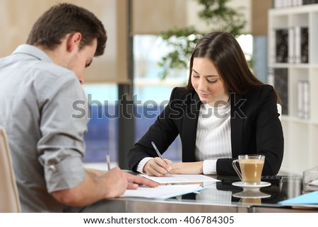 Two businesspeople signing contracts together after a deal in a desktop at office - stock photo