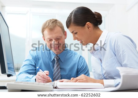 Two businesspeople sitting at table and writing - stock photo