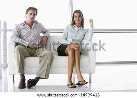 Two businesspeople sitting in office lobby smiling