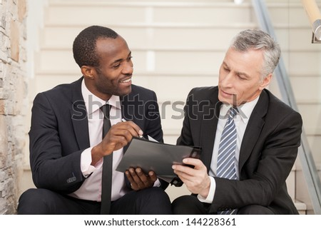 Two businesspeople sitting on stairs and looking at papers. - stock photo