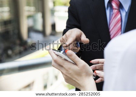 Two businesspeople smiling using smart phone.