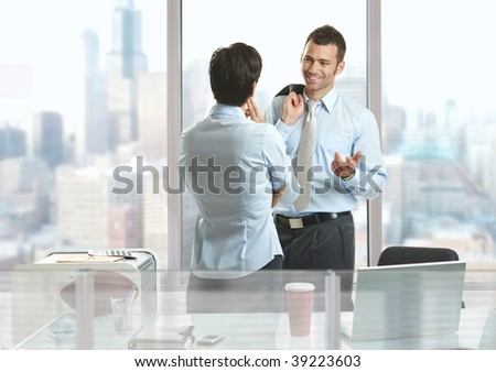 Two businesspeople standing at desk in downtown office building, talking and smiling.