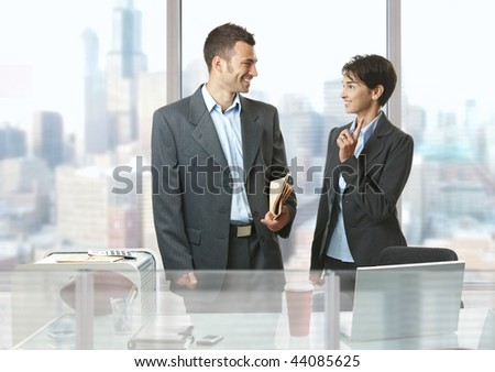 Two businesspeople standing at desk in front of windows in office, talking and smiling. - stock photo