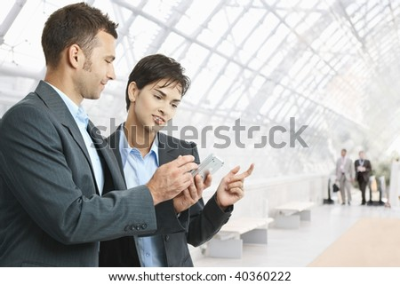 Two businesspeople standing in hallway, looking at mobile phone, smiling. - stock photo