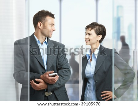 Two businesspeople standing in modern office with glass walls, looking at each other, smiling. - stock photo