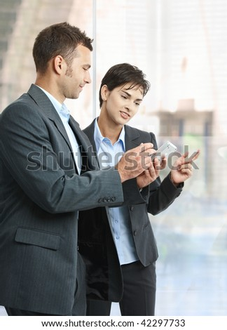 Two businesspeople standing in office lobby using smart mobile phone, smiling. - stock photo