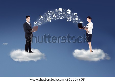 Two businesspeople standing on cloud and share information with laptop computer - stock photo