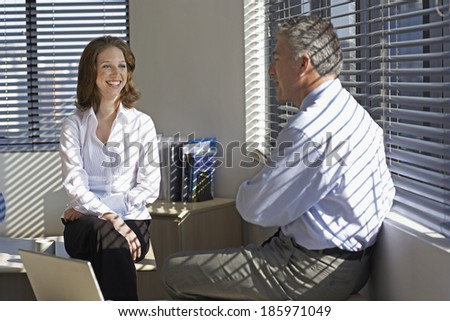 Two Businesspeople Talking by Window - stock photo