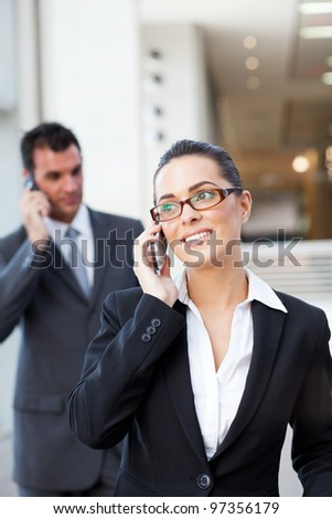 two businesspeople talking on mobile phone - stock photo