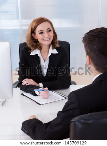 Two businesspeople talking with each other at office - stock photo