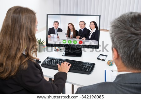 Two Businesspeople Video Chatting With Colleagues On Computer In Office - stock photo