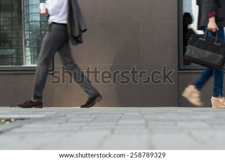 Two businesspeople walking on the street near office building - stock photo