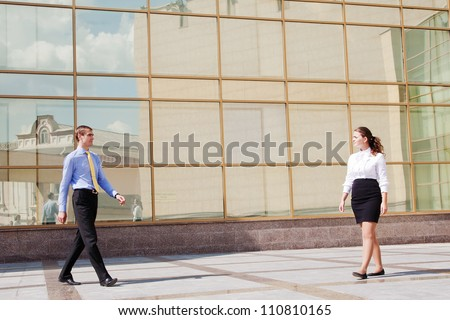 Two businesspeople walking to meet each other near the office building